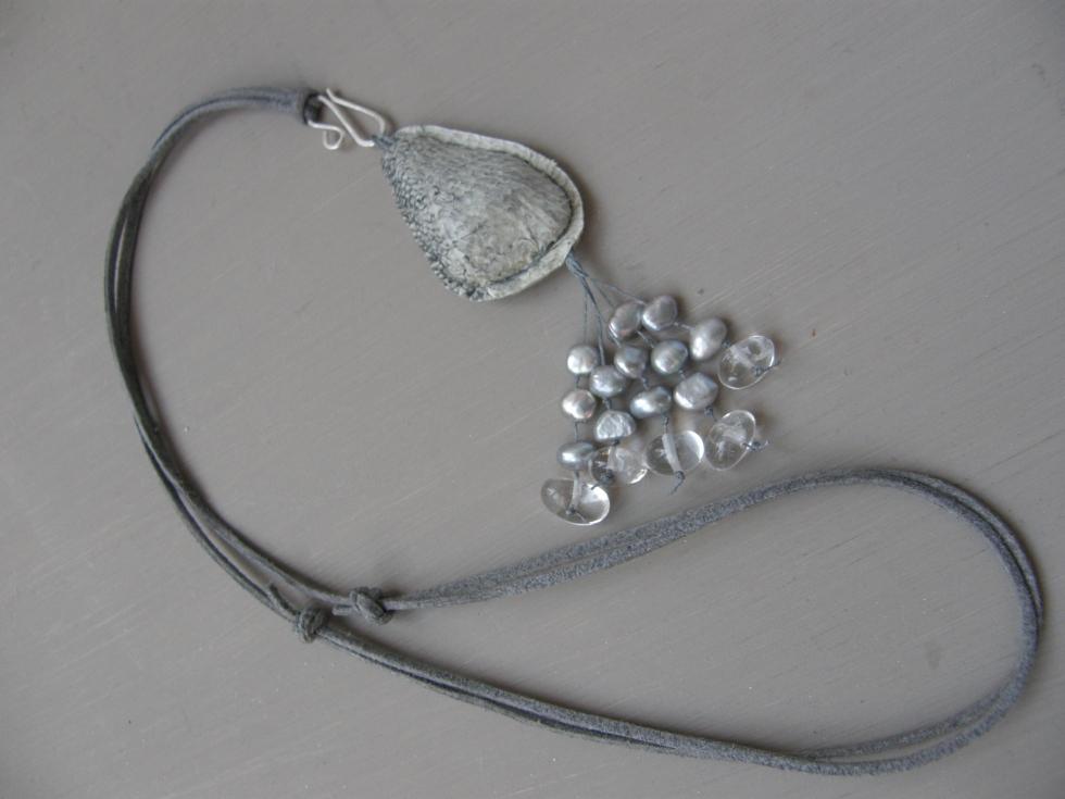 """Halsband i fiskskinn (fettgarvat gös-skinn) och strandsten som tyngd inuti, med fejk-mocka-band, och """"tofs"""" av vaxad lintråd, sötvattenspärlor och bergkristall. """"Kroken"""" är av finsk sterling silver."""