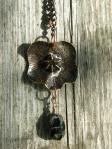 """""""Blomma"""" i svärtad, lackad kopparplåt, med en vanlig sten (kan vara ur en påse sjösten för trädgården, eller från en Hangövägkant), hänge med agat och bronstråd."""