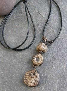 Ceramic beads, bronze wire, leather cord.
