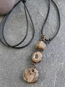 Ceramic beads, bronze wire, leather cord.