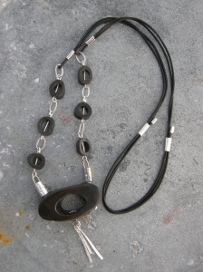 Sterling silver, coffee stained bone, leather cord.