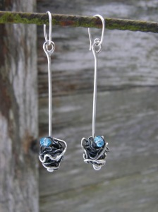 Sterling silver, blackened iron, glass bead.