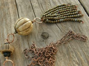 Seed bead and linen yarn tassel, large wooden bead, my own ceramic bead, some Czech glass beads, bronze wire, and copper chain.